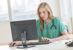 Doctor In Scrubs Using Computer At Hospital Desk. Young female doctor in scrubs using computer at desk in hospital royalty free stock photography