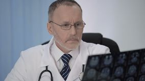 Doctor scrutinizing each part of MRI scan to see if there is reasons for concern. Stock footage stock video footage