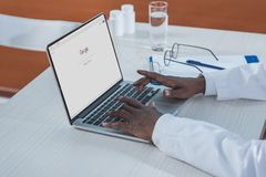 Doctor searching information in Google. Cropped image of african american doctor searching information in Google Stock Image