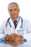 Doctor seated with hands together Stock Photography