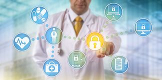 Doctor Securing Data Across Networked Devices. Unrecognizable doctor of medicine securing patient medical records across multiple devices via a computer network Stock Images