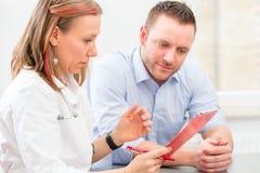 Doctor seeing patient in practice Stock Photos