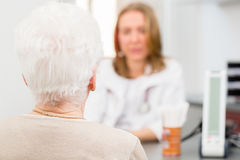 Doctor seeing senior patient in practice Stock Photography
