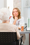 Doctor seeing senior patient in practice Royalty Free Stock Photo
