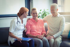 Doctor and senior couple interacting with each other Royalty Free Stock Photos