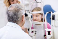 Doctor senior look with eye apparatus in child's eye Stock Photos
