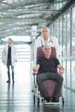 Doctor and senior man patient in wheelchair at hospital corridor royalty free stock photos