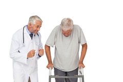 Doctor with senior man using walker Stock Photo