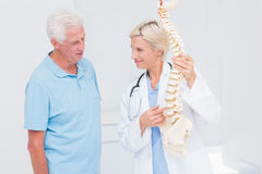 Doctor and senior patient discussing over anatomical spine Royalty Free Stock Photos