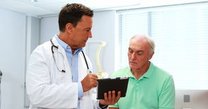 Doctor and senior patient discussing over digital tablet stock footage