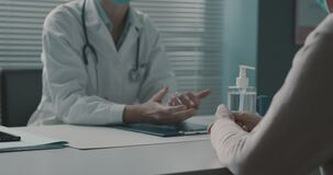Doctor and senior patient talking together in the office