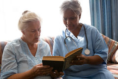 Doctor with senior woman reading book while sitting on sofa. Doctor with senior women reading book while sitting on sofa in nursing home Stock Image