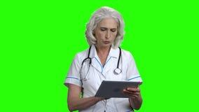 Doctor serio con PC de la tableta en la pantalla verde metrajes