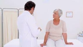 Doctor serio que examina a una mujer madura almacen de metraje de vídeo