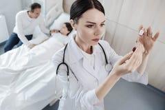 Doctor serio que mira el tubo de ensayo con la sangre de la niña foto de archivo libre de regalías