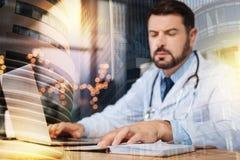 Doctor serio que mira sus notas mientras que trabaja en el ordenador portátil fotos de archivo