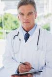 Doctor serio que se coloca con un tablero Fotografía de archivo libre de regalías