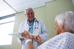 Doctor serving breakfast and medicine to senior patient. In hospital Stock Images