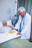 Doctor serving breakfast and medicine to senior patient. In hospital Stock Image