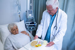 Doctor serving breakfast and medicine to senior patient. In hospital Royalty Free Stock Images