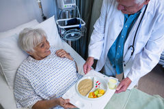 Doctor serving breakfast and medicine to senior patient. In hospital Royalty Free Stock Photo