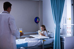 Doctor serving breakfast to girl. In hospital Stock Photography
