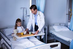 Doctor serving breakfast to girl. In hospital Royalty Free Stock Images