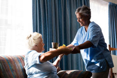 Doctor serving food to senior woman sitting on sofa. Doctor serving food to senior women sitting on sofa in nursing home royalty free stock photo