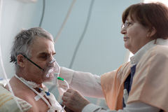 Doctor setting oxygen mask Royalty Free Stock Photo