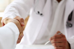 Doctor shake hand as hello with patient in office. Closeup. Welcoming friend, introduction or thanks gesture, consultation work, thankful client talk, team Royalty Free Stock Photo
