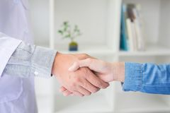 Doctor shakes hands at medical office with patient, wearing glas Stock Photo