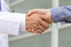 Doctor shakes hands with a patient Stock Images