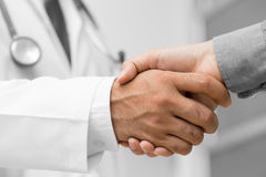 Doctor shakes hands with a patient Stock Photos