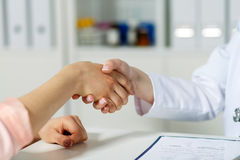 Doctor shaking hand with patient. Female doctor shaking hands with patient. Partnership, trust and medical ethics concept. Handshake with satisfied client Stock Images