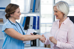 Doctor shaking hands with patient Royalty Free Stock Photos