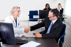 Doctor shaking hands with a patient at a desk Royalty Free Stock Images