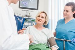 Doctor shaking hands of patient recovering after operation in hospital stock photography