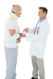 Doctor shaking hands with patient tied up in bandage Stock Photo