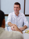Doctor shaking hands to old sick man in clinic Stock Images