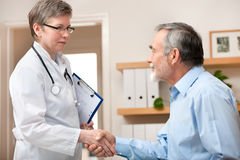 Doctor shaking hands to patient stock photos