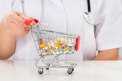 Doctor with shopping cart full of pills Stock Photo