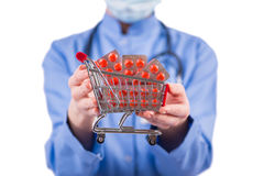 The doctor with shopping cart full of pills isolated on white Stock Photography