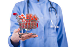 The doctor with shopping cart full of pills isolated on white Royalty Free Stock Photography