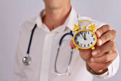 Doctor Showing Alarm Clock close up. It's Time to find time for your Health Stock Photography