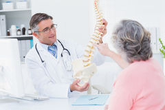 Doctor showing anatomical spine while patient touching it. Male doctor showing anatomical spine while female patient touching it in clinic stock photography