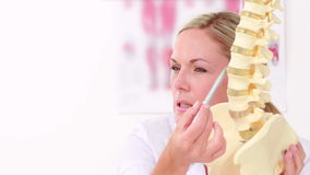 Doctor showing anatomical spine to her patient. In medical office stock footage
