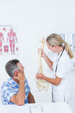 Doctor showing anatomical spine to her patient Stock Photography