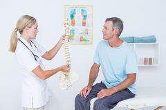 Doctor showing anatomical spine to her patient. In medical office royalty free stock photos