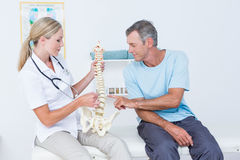Doctor showing anatomical spine to her patient Stock Images