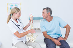 Doctor showing anatomical spine to her patient Royalty Free Stock Photos